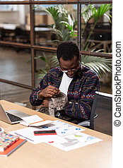 Man holding the gray cat while working
