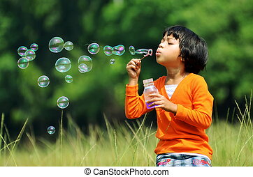 Playing with bubbles - Children playing with soap bubbles on...