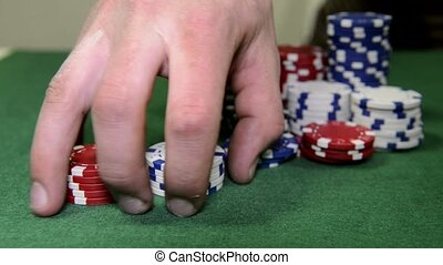 Playing with chips - Poker player fiddling with a stack of...