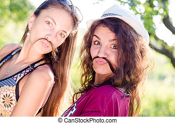 playing with hair like mustache 2 beautiful brunette young women best friends having fun looking at camera on green summer outdoors copy space background, closeup portrait