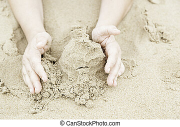 Playing with hands in the sand