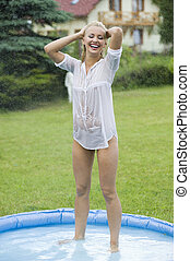playing with water - blond girl with wet shirt inside a...