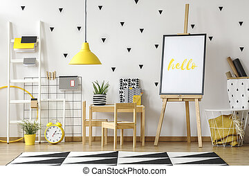 Playroom and study corner for a child in a fun room interior with wooden furniture, yellow lamp and black stickers on a white wall