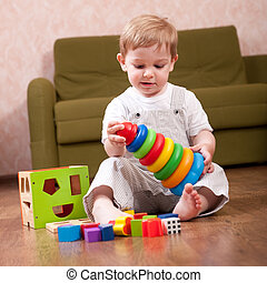 Playtime in playroom - Little boy is playing with toy blocks