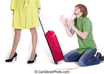 crying man on knees pleading to woman with luggage