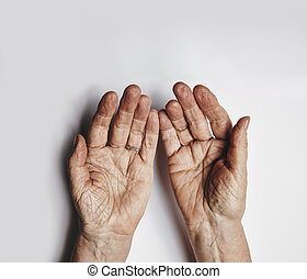Top view of two empty female hands over grey background. Senior woman hands pleading. Wrinkled palms of aged woman with copy space.
