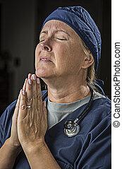 Pleading in Prayer Female Doctor or Nurse