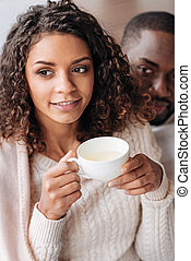 Pleasant African American couple drinking tea in the cafe