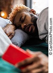 Pleasant African American man hearing the alarm clock
