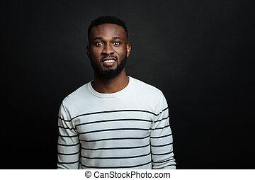 Pleasant African American man smiling in the studio