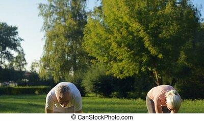 Pleasant aged couple enjoying breathing exercises -...