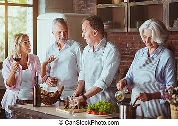 Pleasant aged couples cooking in the kitchen
