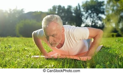 Pleasant aged man doing push ups in the park