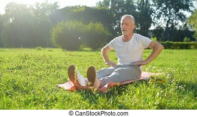 Pleasant aged man doing stretching exercises on the exercise...