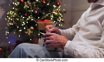 Pleasant aged man preparing Christmas presents
