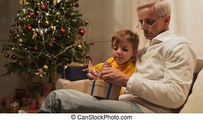 Pleasant aged man preparing Christmas presents with his cute grandson