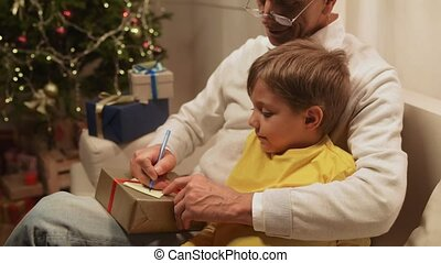 Pleasant aged man preparing Christmas presents with his grandson