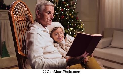 Pleasant aged man reading a book with his little grandson