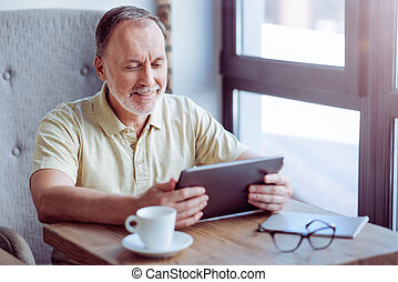 Pleasant aged man sitting in the cafe