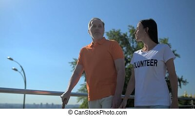 Pleasant aged man walking with a positive female volunteer