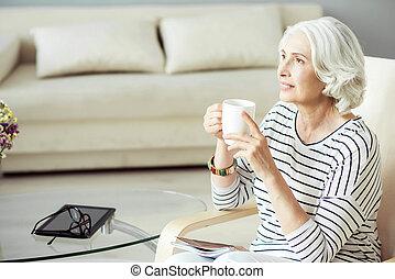 Pleasant aged woman drinking tea