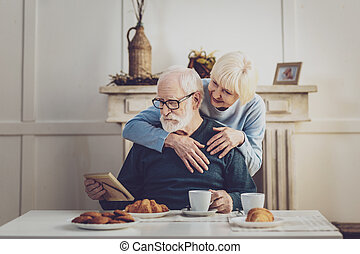 Pleasant aged woman supporting her husband