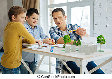 Pleasant architect explaining his landscape architecture project to sons