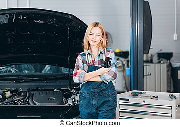 pleasant attractive fair-haired confident mechanic standing in front of the broken car, close up portrait. hobby, occupation