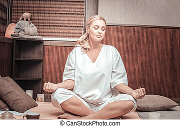 Pleasant attractive woman sitting in the lotus pose
