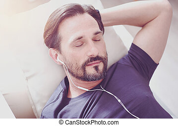Pleasant bearded man resting at home