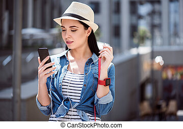 Pleasant beautiful woman holding cell phone