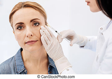 Pleasant blonde woman having a botox injection