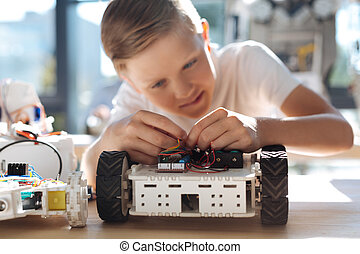 Pleasant boy connecting wires in robotic vehicle