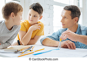 Pleasant boys talking with father while he working on blueprint