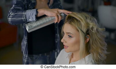Pleasant business woman with make-up in a beauty salon. Professional hairdresser makes hairstyle for blondes.