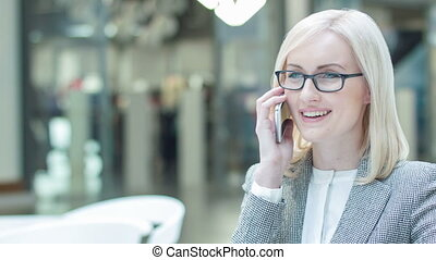Pleasant businesswoman having a phone talk.