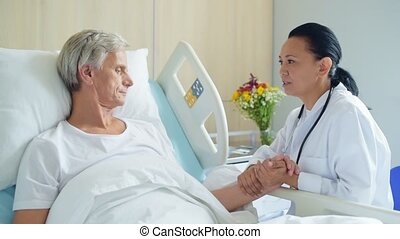 Pleasant caring doctor supporting his aged inpatient - We...