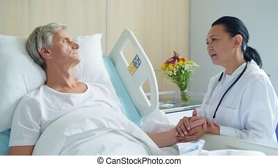 Pleasant caring doctor talking with a sick aged man