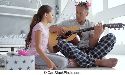 Pleasant caring father playing the guitar at home - Happy...
