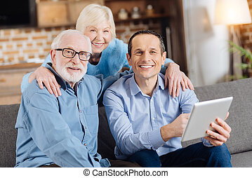 Pleasant cheerful family smiling at camera while son using tablet