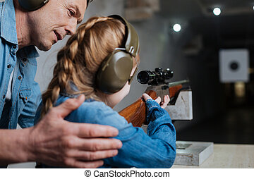 Good job. Pleasant cheerful nice man holding his daughter and teaching her how to shoot while helping her