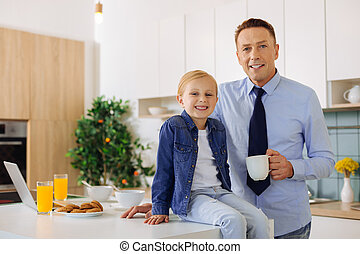 Pleasant cheerful man standing near his daughter