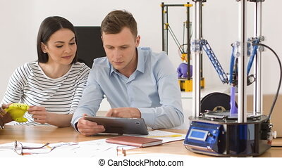 Pleasant colleagues using 3d printer