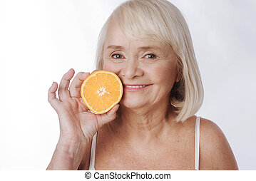 Pleasant content woman holding an orange half