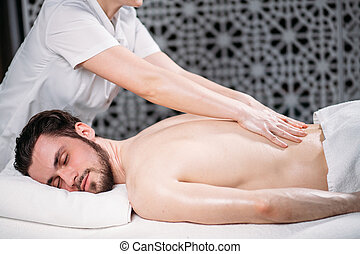 pleasant dark-haired guy is getting massage for spine