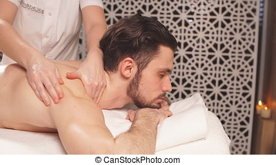 Pleasant dark-haired guy is getting massage for spine.spine...
