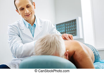 Pleasant delighted doctor standing near his patient