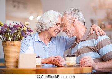 Pleasant delighted senior couple bonding to each other.