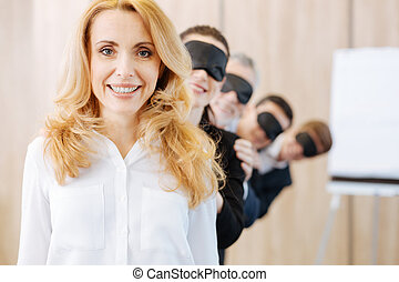 Pleasant delighted woman standing in front of her colleagues