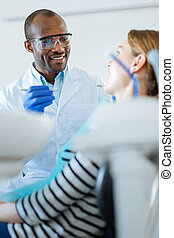 Pleasant dentist having pleasant conversation with his patient
